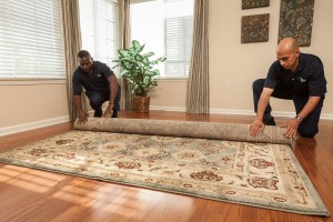 servicemaster techs rolling an area rug in wichita ks